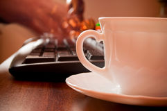 Coffee and hands on the keyboard Royalty Free Stock Images