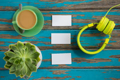 Coffee with headphones, sticky notes and pot plant on table Stock Images