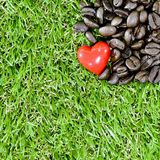 Coffee heart. Closeup red heart and coffee beans on green grass background Stock Photos