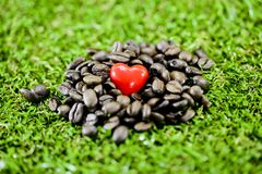 Coffee heart. Closeup red coffee on coffee beans on green grass background Royalty Free Stock Images