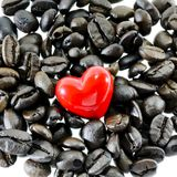 Coffee heart. Closeup red heart on coffee beans on white background Royalty Free Stock Photography