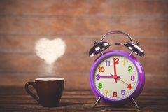 Coffee with heart shape steam and alarm clock Stock Photos