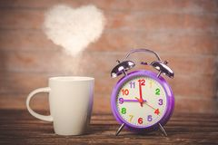 Coffee with heart shape steam and alarm clock Royalty Free Stock Image