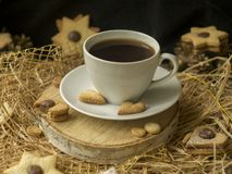 Coffee and a heart shaped cookie on a wooden saw on a black background. Breakfast for her on Valentine`s Day. Cookies stock photo