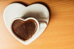 Coffee in heart shaped cup mug. Caffeine energy. Stock Photos