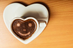 Coffee in heart shaped cup with smile face sign Stock Image