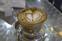 Coffee with heart. And spoon on table Royalty Free Stock Photography