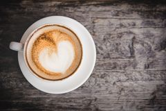 Coffee with heart on a white saucer, old wood background, Royalty Free Stock Photos