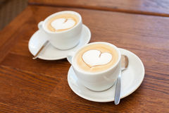 Coffee with hearts. Two cups of coffee on a table with a foam heart shape Royalty Free Stock Photography