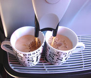 Coffee home making. Making coffee at home with espresso machine. Shoot while coffee is falling in the cups Royalty Free Stock Photography