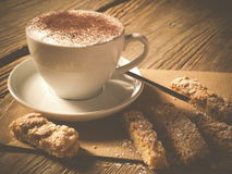 Coffee with homemade biscotti. Photo shows a cup of coffee with nice crema decorated with homemade almond biscotti situated on an old wooden table Royalty Free Stock Photography