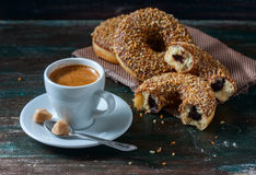 Coffee and homemade donuts with chocolate and nuts on a dark wooden background. Stock Photos