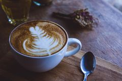 Coffee hot drink cappucino latte art on wood vintage table , cof stock photography