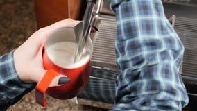 Coffee house.Barista making cappuccino. Making espresso and steam milk. Barista at work preparing hot milk foam. Slow stock footage