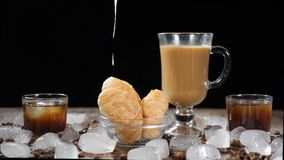 Coffee house with delicious croissants on glass plate. Hot clear liquid honey pouring down on dessert in slow motion. Cup of aromatic latte on the background stock video footage