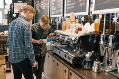 Coffee house, small business, male barista near the coffee machine. Experienced barista coaching teaching young man to brew coffee royalty free stock photography