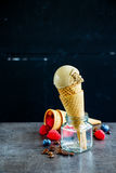 Coffee ice cream. Delicious coffee ice cream in waffle cone with fresh raspberries and blueberries, rustic wooden wall background, selective focus. Healthy Royalty Free Stock Photography