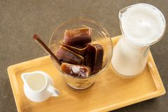 Coffee in ice cube shape with steam milk and syrup. On wooden plate. Frozen coffee cube Royalty Free Stock Photos