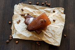 Coffee ice lolly. Homemade coffee ice lollypop on a parchment Royalty Free Stock Photos