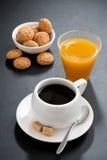 Coffee, italian cookies and orange juice on black background Stock Images