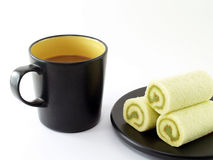 black coffee cup with hot coffee and green jam roll cakes on black plate isolated on white background Stock Images