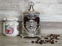 Coffee jars on bleached oak wooden shelf porcelain and glass silver vintage sterling. Classic renaissance ornament and paintings. Hand-made. Coffee beans royalty free stock photography