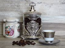 Coffee jars and a cup of coffee on bleached oak wooden shelf porcelain and glass silver vintage sterling. Classic renaissance ornament and paintings. Hand-made royalty free stock photos