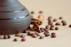 Coffee beans, ceramic Turk and cinnamon sticks on a beige background. royalty free stock photos