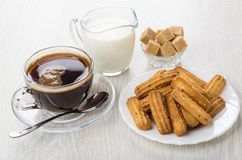 Coffee, jug of milk, sugar, shortbread cookies with sesame. In plate and spoon on wooden table Royalty Free Stock Photos
