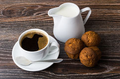 Coffee, jug milk and three muffins on wooden table. Coffee, jug milk and three muffins on black wooden table Stock Image