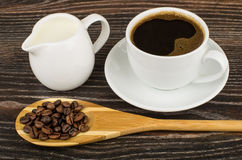 Coffee, jug milk and wooden spoon with coffee beans. On dark table Stock Photos