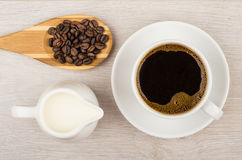 Coffee, jug milk and wooden spoon with coffee beans Royalty Free Stock Photos