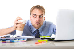 Coffee junkie businessman holding take away cup looking with crazy eyes and funny face expression overworked. Working at office computer desk in caffeine royalty free stock images