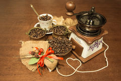 Coffee and jute. Coffee seeds in copper bowls with ceramic cup and grinder with composition jute Stock Photo