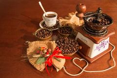 Coffee and jute. Coffee seeds in copper bowls with liquid coffee cup and coffee grinder near a composition jute Stock Images
