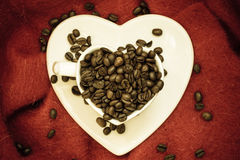 Coffee klatsch java concept. Heart shaped cup filled with roasted coffee beans. Coffee klatsch java concept. Heart shaped white cup filled with roasted coffee Stock Image