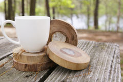 Coffee at the lake house. White cup balancing on wooden circles at a forest camp site Stock Photography