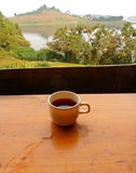 Coffee with a Lake View. A cup of coffee sitting on a table overlooking a tropical lake view Royalty Free Stock Photography