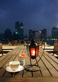 Coffee and lamp. On a table of an outdoor bar with night scene background Royalty Free Stock Photos