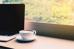 Coffee and laptop on desk bar in cafe with drink in morning. Stock Photo