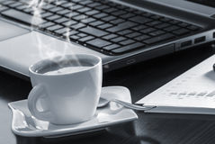 Coffee and laptop. Open black laptop and hot cup of coffee on wood table stock photos