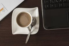 Coffee and laptop. Open black laptop and hot cup of coffee on wood table stock photography