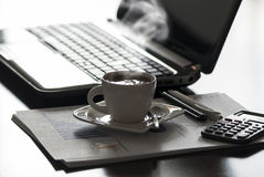 Coffee and laptop. Open black laptop and hot cup of coffee on wood table royalty free stock image