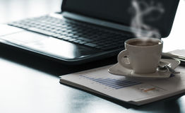 Coffee and laptop. Open black laptop and hot cup of coffee on wood table stock photo