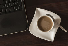 Coffee and laptop. Open black laptop and hot cup of coffee on wood table royalty free stock photo