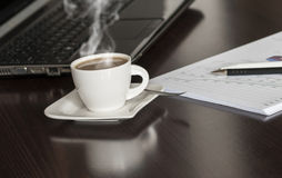 Coffee and laptop. Open black laptop and hot cup of coffee on wood table royalty free stock photography