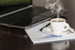Coffee and laptop. Open black laptop and hot cup of coffee on wood table royalty free stock images