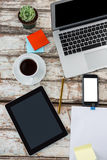 Coffee, laptop, pot plant, sticky notes and mobile phone on wooden table Stock Images