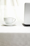 Coffee and laptop on white tablecloth Royalty Free Stock Photography