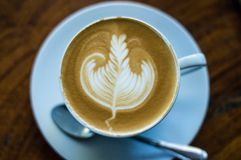 Coffee Latte Art, a leaf on a white plate stock photos